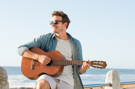guys: Handsome young man wearing sunglasses and playing guitar on fence near beach. Smiling guy playing acustic guitar at sunset. Carefree man looking away at sea shore.