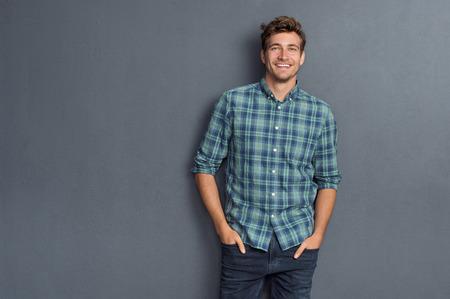 Przystojny młody człowiek na szarym tle patrząc na kamery. Portret śmiechem młody człowiek z rękami w kieszeniach pochylony przed szarą ścianą. Szczęśliwy człowiek uśmiechnięty.