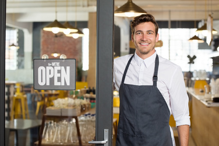 shop sign: Portrait of smiling owner standing at his restaurant gate with open signboard. Young entrepreneur leaning at the cafeteria door and looking at camera. Chef or waiter standing in front of coffee shop.