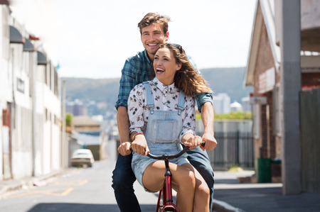 riding: Happy young couple riding on a bicycle together. Beautiful happy girl sitting on a bike tube while her boyfriend riding a bike on the street. Laughing young man and young woman having fun on bike. Stock Photo