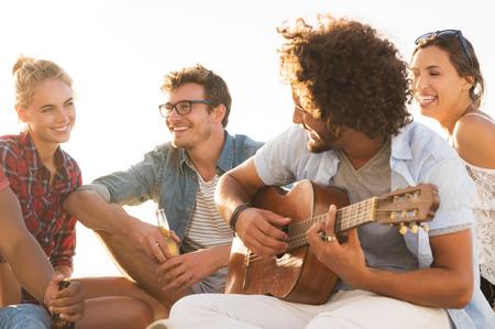 jovenes felices: Feliz amigos se divierten juntos mientras tío tocando la guitarra. Grupo de mujeres y hombres jóvenes que disfrutan de sus vacaciones de verano. Alegre joven tocando la guitarra y sus amigos cantando al atardecer. Foto de archivo
