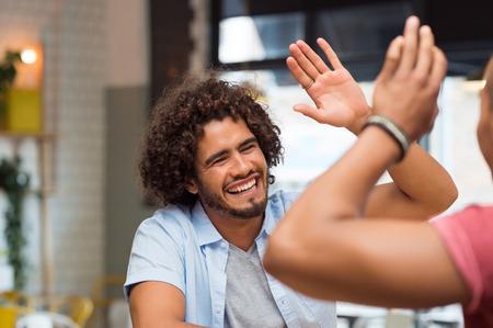 Portret van vrienden die hoogte vijf bij cafe terwijl lunchen. Jonge kerels vrienden het geven van een high five, slapping elkaars hand in felicitaties tijdens de vergadering in de cafetaria.
