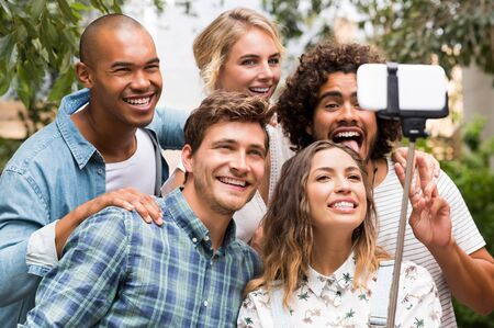 funny guys: Happy friends with funny face taking a photo with a selfie stick. Group of smiling guys and girls taking picture by smartphone. Happy and cheerful young men and beautiful girls taking a selfie outdoor.