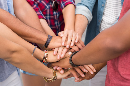 stacked up: Close up of friends with their hands stacked. Closeup of friends making pile of hands outdoor. Young multiethnic people putting their hands on top of each other symbolizing unity and teamwork. Stock Photo