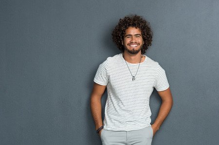 Portrait of happy young man with curly hair standing against grey background. African man with hands in pocket leaning against grey wall. Multi ethnic young man in casual looking at camera with copy space.