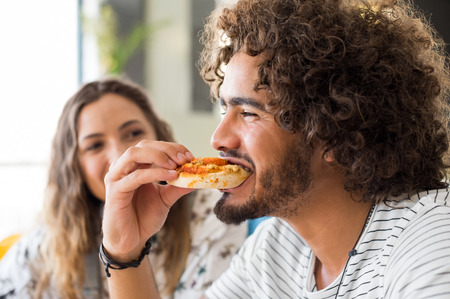 Close up face of a young african man eating a pizza in a coffee shop. Happy guy with friends enjoying brunch in a cafeteria. Portrait of a multiethnic young man biting pizza. Foto de archivo