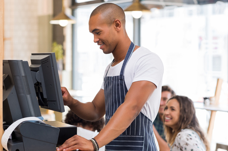 Happy young waiter in blue apron checking bill before printing it. Young african waiter printing bill in cafeteria. Waiter printing order on digital cash register. Stock Photo