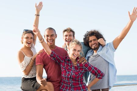 exult: Group of friends having fun together and looking at camera. Young cheerful group of young men and women exult with arms outstretched. Laughing couples with friend standing together at sunset.