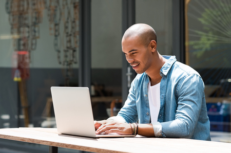 Happy man writing text on laptop in a modern coffee shop. Happy african student surfing the web on laptop with wireless free connection. Smiling guy in casual studying on laptop sitting outdoor the cafe. Stock Photo