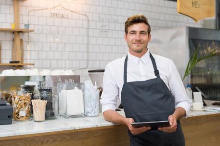 propietario de la pequeña empresa exitosa celebración de la tableta digital y mirando a la cámara. camarero sonriente feliz con el delantal y la tableta digital apoyándose en el mostrador. Retrato de joven empresario de cafetería posando.
