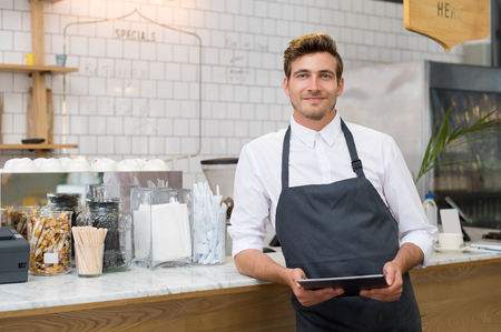 Successful small business owner holding digital tablet and looking at camera. Happy smiling waiter with apron and digital tablet leaning on counter. Portrait of young entrepreneur of coffee shop posing.