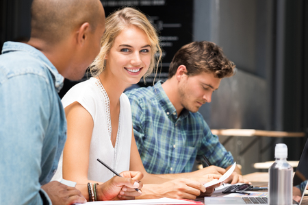 Close up of young woman looking at camera while her friends studying. Team of students preparing for university exam. Portrait of beautiful blonde girl with her friends studying outdoor in a summer day.