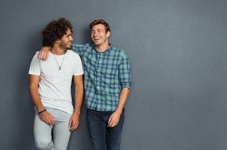 casual wear: Two friends in casual wear standing and laughing together. Best friends enjoying isolated over grey background. Two men having fun isolated over grey wall with copy space.