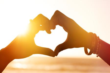 Srdce tvar rukama proti moři při západu slunce. Zblízka srdce z prstů na pláži. Ruku v podobě lásky srdce na slunečním světle pozadí, siluetu. Reklamní fotografie