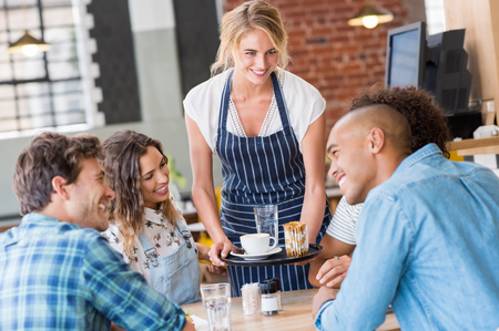 cafeteria tray: Happy smiling waitress serving food to a young happy group of friends in a cafeteria. Waitress serving on tray coffee to customers. Happy satisfied woman serving capuccino to group of multiethnic students. Stock Photo