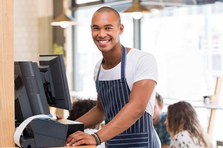 Portrait der freundlichen Kellner jung, die Kamera beim Rechnungsdruck. Glücklich lächelnd Kellner für Rechnung warten, um zu drucken. African Kellner in Cafeteria und die Quittung gedruckt wird. Standard-Bild