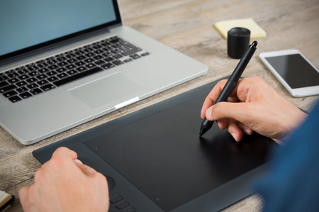 pen tablet: Close up hand of graphic designer drawing on pen tablet at the office. Hand working with graphic tablet on desk with laptop. Close up of man using pen on graphic tablet to complete editing work.