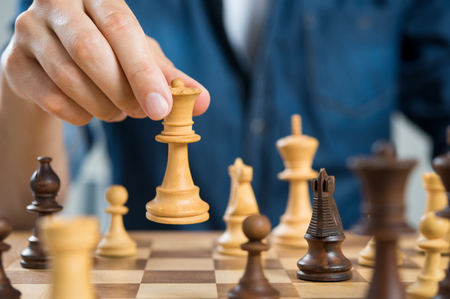 move in: Close up of hand of man playing chess holding queen. Business man playing chess. Hand of casual businessman making a move with queen in chess. Business strategy and leadership concept. Stock Photo