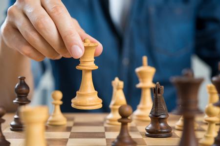 Sluit omhoog van hand van de koningin van de schaakholding van het mensen speelschaak. Zakenman Schaken. Hand van toevallige zakenman die een beweging met koningin in schaak maakt. Bedrijfsstrategie en leiderschap concept.