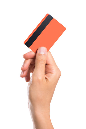 male hand: Hand holding credit card isolated on white background. Close up of a man hand holding up a creditcard. Male hand showing orange credit card with magnetic strip. Stock Photo
