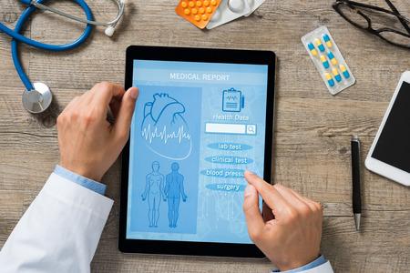 디지털 태블릿에 의료 보고서를 검사하는 의사 손의 높은 각도보기. 의사가 환자의 건강 기록을 확인하면서 옵션을 선택합니다. Mediacal 보고서를 검토 스톡 콘텐츠