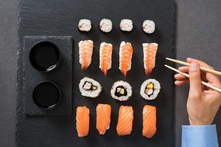 Top view of man eating sushi roll with chopsticks at restaurant. Close up of hand holding chopstick ready to eat japanese food. High angle view of young businessman eating sushi served on a black plate. Фото со стока