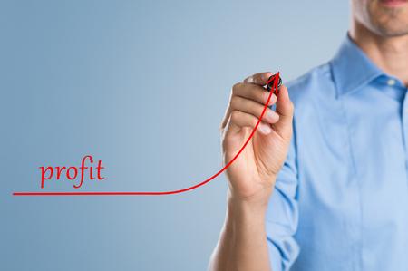 Cierre de negocios usando marcador para dibujar un gráfico de crecimiento. Primer plano de marcador de celebración mano del hombre aislado en un fondo azul. Exitoso hombre de negocios aumentar sus beneficios.