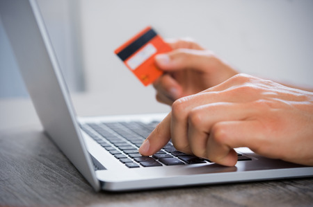 paying the bills: Closeup hand of man typing credit card details on laptop to complete payment process. Close up of male hand paying bills online with laptop and credit card. Hand holding credit card and using computer. Internet banking. Stock Photo
