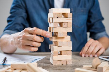 konzepte: Geschäftsmann über neue Herausforderung zu denken. Close up von Hand des Menschen ein Stück Bau von Holzklötzen nehmen. Geschäftsmann versucht, eine Lösung des Problems zu finden, indem sie mit Holzklötzen zu bauen. Risiko- und Strategiekonzept.