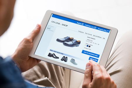 Hombre joven que mira los zapatos en línea. Hombre en busca de diversas opciones de zapatos a través de Internet a través de la tableta digital. Hombre ocasional que hace que las compras en línea en casa con tableta digital.