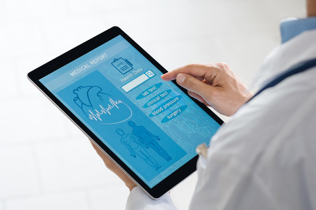 patient data: Close up of doctor checking patient data on digital tablet. Doctor selecting options checking patient health history. Young doctor holding digital tablet at hospital to review report.