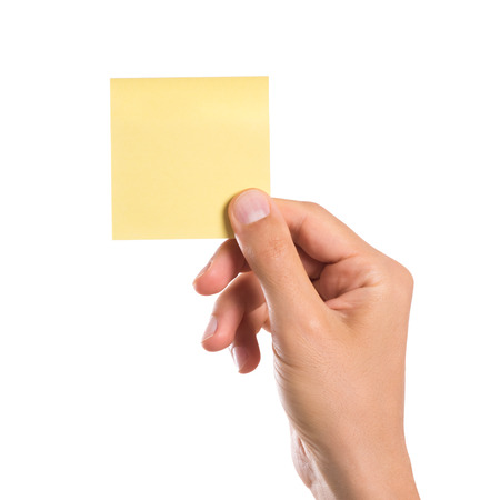 postit: Male hand holding a yellow empty sticky note isolated on white background. Man hand holding blank yellow notepaper on white background. Close up of hand showing square post it.
