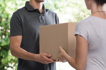 Vrouw en koeriersdiensten in orde overdracht. Vrouw te accepteren levering uit bezorger. Bebouwd beeld van delivery service werknemer geven pakket aan opdrachtgever. Stockfoto