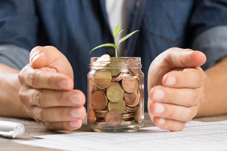 frasco: Cerca de las manos del hombre de proteger la planta crece de la pila de monedas. El hombre de negocios cuidar de planta que brota de una pequeña jarra llena de dinero. La inversión empresarial, el crecimiento y el futuro concepto de finanzas.