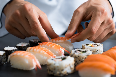 Closeup of chef hands preparing japanese food. Japanese chef making sushi at restaurant. Young chef serving traditional japanese sushi served on a black stone plate. Stock Photo