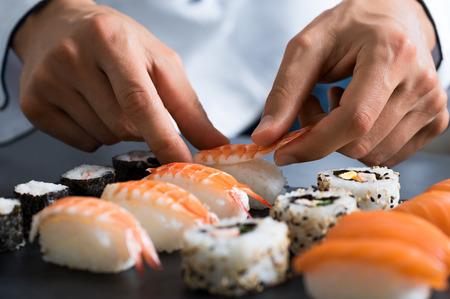 gamba: Detalle de las manos del cocinero que prepara comida japonesa. chef japonés hacer sushi en el restaurante. Joven chef que sirve sushi japonés tradicional que se sirve en una placa de piedra negro.