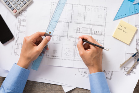 architect drawing: Top view of architect drawing new project on blueprint. Closeup of man hands working and sketching a construction project on office desk. Project of new house.
