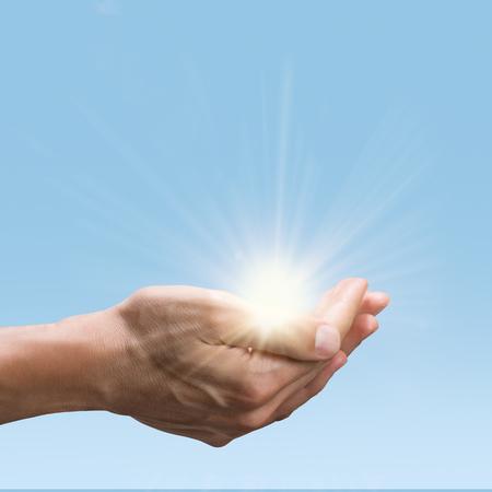 Gros plan des mains de l'homme tenant un soleil éclatant. Geste de la paume ouverte de la main masculine tout en maintenant l'énergie verte du soleil. Conservation de l'environnement et concept d'énergie verte.