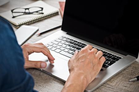 Close-up van de hand van zakenman te typen op een laptop toetsenbord. Hand man het schrijven van een e-mail op een moderne laptop in een kantoor. Close-up van de hand van casual zaken man te typen op de computer en zit op houten bureau.
