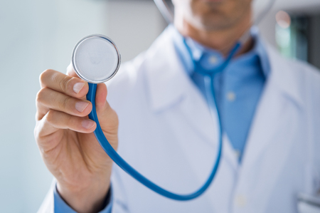 auscultate: Male doctor showing stethoscope for checkup. Close up of doctor hand holding stethoscope to auscultate breath. Doctor with stethoscope in hand on hospital background for medical visit.