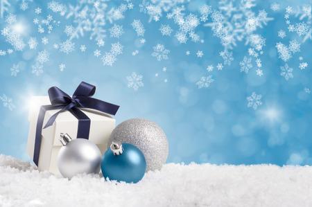 cadeau de Noël enveloppé avec ruban bleu avec des boules d'argent sur la neige blanche. Petit cadeau de Noël sur la neige avec copie espace sur fond bleu. Bleu et argent noël décoration avec copyspace.