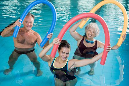 Porträtt av leende människor gör aqua fitness tillsammans i en pool. Grupp av äldre kvinna och mogen man med simma nudlar som tränar i en simbassäng. Ung tränare och seniorer i gymnastiksal gymnastiksal. Stockfoto