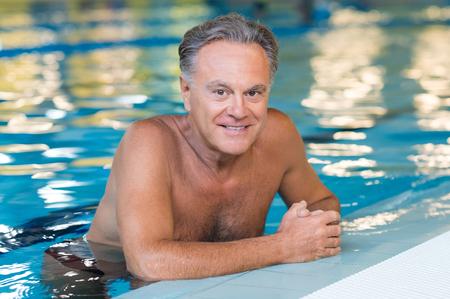 Aktiver älterer Mann in die Kamera in einem Schwimmen im Pool. Gesunde alte Mann im Pool schwimmen. Glücklicher Rentner genießen sportlichen Lebensstil.