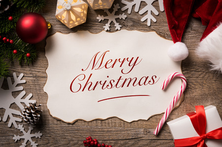 wood sign: High angle view of Santa Claus letter with Merry Christmas text on it. Top view of merry Christmas xmas wish list with little gift present and santa claus hat on wooden background. Stock Photo