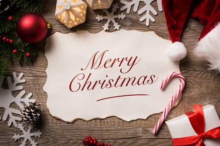 Vista de ángulo alto de la carta de Santa Claus con el texto Feliz Navidad en él. Vista superior de la lista de deseos de Navidad Feliz Navidad con el pequeño regalo presente y sombrero de Santa Claus en el fondo de madera.