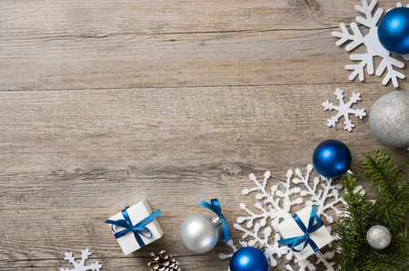 Christmas background with decorations and white gift boxes with blue ribbon on wooden table with copyspace. Top view of xmas decorations with fir branches, snowflakes, christmas blue and silver balls and presents.