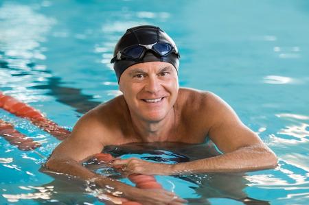 풀을 들고 풀에서 서 수석 남자 웃 고. 수영 모자와 카메라를 찾고 고글을 착용하는 성숙한 남자의 초상화. 수영장에서 자랑스럽고 활동적인 은퇴 한