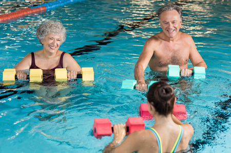 Senior couple in training session of aqua aerobics using dumbbells in swimming pool. Mature man and old woman practicing aqua fitness together. Healthy and fit senior couple enjoying their retirement in aqua aerobics training.