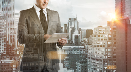 Double exposure image of a modern businessman with digital tablet over a city view. Business man with modern tablet with skyskrapers in background during the morning sunlight. New technology concept. photo
