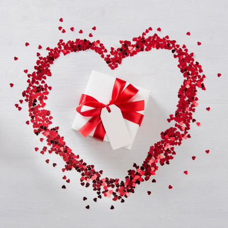 High angle view of romantic gift box wrapped in red ribbon on white wooden table. Top view of little hearts form one big heart with a present with greeting card in the center. Valentine day and love concept.